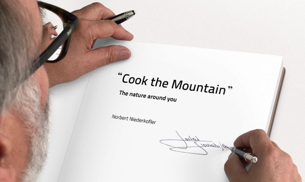 Norbert Niedekofler as he signs a copy of his Cook the Mountain - The nature around you, the book summarising the ideas of the chef from South Tyrol which permeate the fantastic food at his St.Hubertus, three stars in San Cassiano