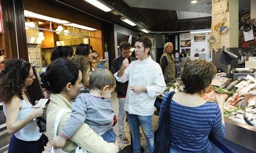 Riccardo Orfino del ristorante Ladybù spiega ai clienti del mercato Wagner tutti i segreti del suoSgombro marinato all'aceto di moscato, centrifugato di scarti di verdure e panzanella, 200 piatti venduti sabato in occasione di Tutti a Tavola a Milano!, evento concepito da Comune di Milano e Identità Golose. Con Wagner, l'evento ha animato anche i mercati di Prealpi, Fusina, Gratosoglio, Morsenchio, Ferrara, Rombon e Zara(foto di Francesca Brambilla e Serena Serrani)