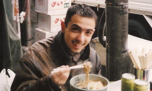 Un giovanissimo Riccardo Monco si gusta un piatto di udon nei pressi del mercato del pesceTsukiji di Tokyo