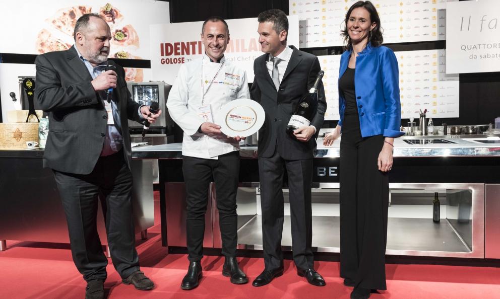 Marco Amato riceveil premioIdentità di SaladaCamilla LunellidiCantine Ferrari. Sul palco anche lo chef Francesco Apreda
