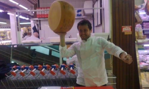 Alessandro Negrini in piazza Wagner si diverte a giocare con una forma di Grana Padano