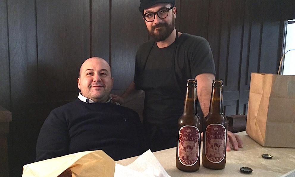 Alessandro Pipero seduto dietro al banco all'ingresso del nuovo ristorante che a Roma ha preso il posto del Pipero al Rex vicino alla Stazione Termini. In piedi accanto a lui lo chef Luciano Monosilio