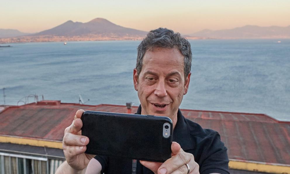 Daniel Young con alle spalle il golfo diNapoli e il Vesuvio, in una foto di Luciano Furia. Il giornalista americano ha pubblicato nel 2016 Where to eat pizza per Phaidon, una specie di atlante delle pizze più buone del pianeta. Delle 20 migliori pizzerie al mondo, 10 erano italiane, di cui 7 nei primi 10 posti