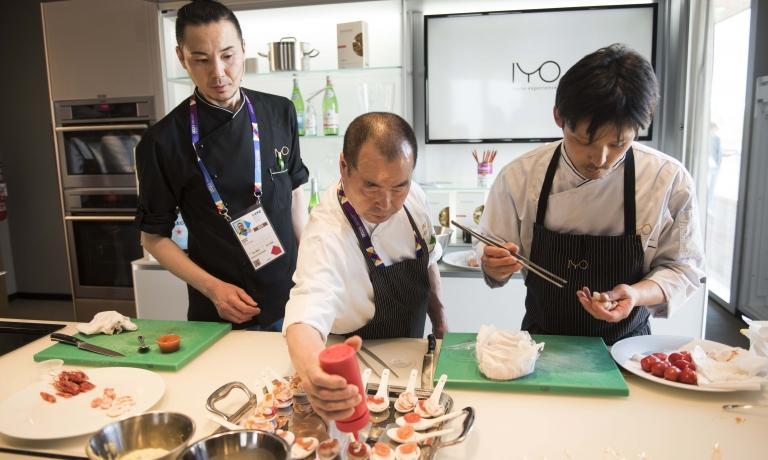 Lo chef Haruo Ichikawa, in mezzo a due assistenti, durante una recente lezione nel temporary restaurant di Identità Expo S.Pellegrino