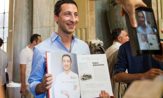 Abbattista posa con aperte le pagine a lui dedicate, in 100 chef x 10 anni (Mondadori)