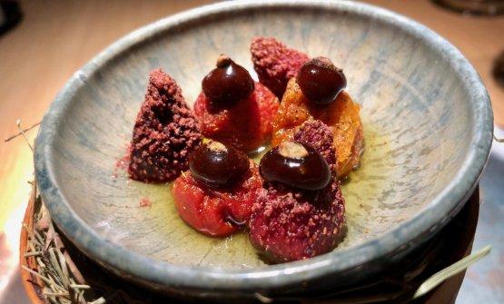 """Dried autumn fruits with rabbit sauce and toffee Frutti d'autunno con salsa e toffee di coniglio. Sono pomodori e fragole messe via l'estate scorsa. Dentro le fragole c'è unapasta dipesto di mele cotogne selvatiche, prugnolo e semi di coriandolo. L'olio di coniglio arrostito - sapido, acido, molto piacevole -è un'idea di Canella, che si rifa all'intingolodella mamma delladomenica, qui traslato con spezie nordiche. La toffee è una riduzione di caramello fattacon le ossa dell'animale piùmela efungo. La polvere che si intravede nasce dalla pelle essiccata delleprugne fermentate, frullate poicon pepe nero e timo artico (""""Sembra un pepe rosa, è pazzesco"""", si illumina il cuoco padovano). Piatto geniale"""
