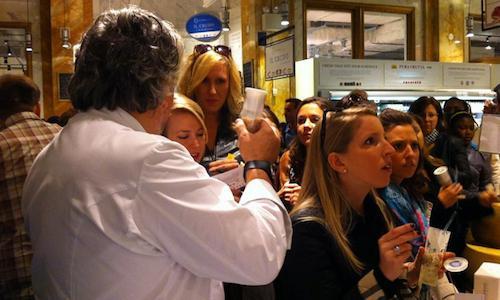 Di spalle, Davide Scabin mostra a una fila di curiose i suoi Maccaroni and cheese da shakerare nello spazioFelicettidi Eataly New York. Un successone (foto del servizio di Francesca Brambilla e Serena Serrani)
