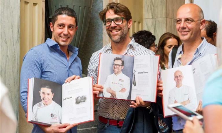 Renato Bosco (al centro) con Ciro Salvo e Franco Pepe con la sua copia di 100 chef x 10 anni, il libro che racconta l'evoluzione della cucina italiana e che sarà raccontato domani, venerdì 6 maggio, in apertura di Esperienze Gustose, la nuova kermesse sul cibo che prenderà avvio a Verona, alla quale anche Bosco è atteso