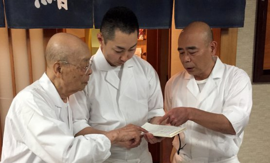 Jiro and his son Yoshi (54, to the right) look for a place for Bottura in the reservation book