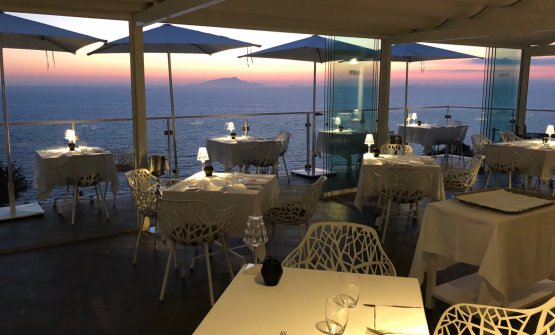 I 20 coperti del ristorante La Terrazza al tramonto. Sullo sfondo, Capri, Ischia e Procida