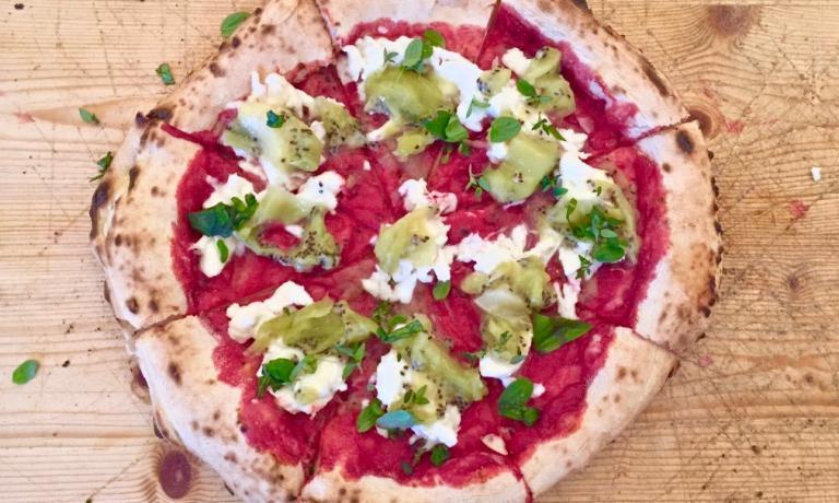 La squisita pizza con salsa di barbabietola, kiwi, bufala e trito di timo, maggiorana, basilico