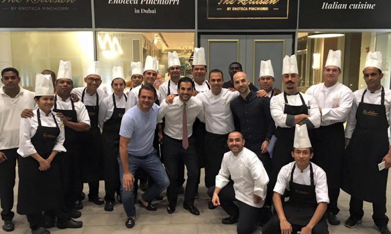 """Foto di gruppo, questa volta della brigata di cucina. In piedi si riconoscel'executive chef Luca Tresoldi (al centro, abbracciato ai proprietari libanesiFiraseHassan Fawaz). Accosciato in casacca bianca,Riccardo Monco, primo chef a Firenze e co-responsabile della linea di cucina di Dubai (""""Con Luca siamo sempre su Skype"""", spiega)"""