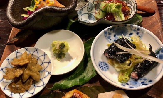 Gli antipasti misti in apertura (Aki no zensai moriawase). In senso orario, dall'alto: Salmone marinato con verdure di stagione e salza tozasu; Involtino di hakusai (cavolo cinese) con fagiolini, pasta di sesamo e salsa Ohitashi; Isobe Age cioè fritto di alga nori con calamaro e gambero; Sgombro marinato e grigliato con sake, mirin e patata taro e Chips di soba in forma di foglie di cero,gingko,