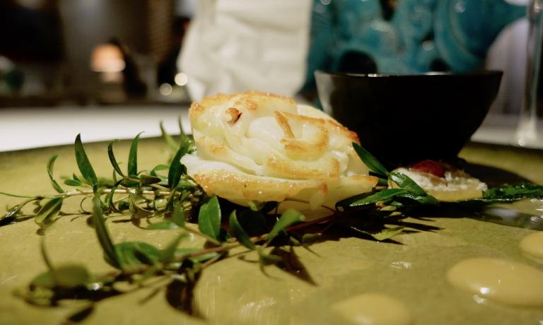 Calamaro arrostito (su brace aromatizzata con rosmarino e mirto), infuso di calamaro (ottenuta con l'acqua di cottura dei tentacoli e della pelle), salsa alle erbe verdi e alle radici, daikon e parmigiano