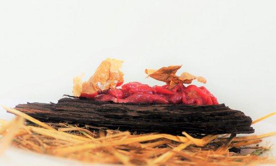 Bistecca Primitiva: manzo della Garfagnana stracciato al coltello e insaporito con il suo grasso cotto in padella, servito con bucce di patata fritta e posto su corteccia di pino marittimo