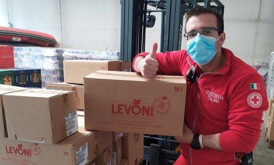 Un operatore della Croce Rossa di Bergamo mostra alcuni dei pacchi ricevuti da Levoni