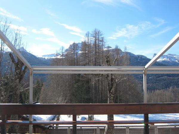 Seduti a un tavola della terrazza panoramica di Baita Fraina a Cortina d'Ampezzo, telefono +39.0436.3634, lo sguardo spazia su monti dolomitici di straordinaria bellezza. Da sinistra verso destra, tra i rami degli alberi, si possono distinguere Becc� di Mezzod�, Croda da Lago e Nuvolao