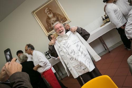 Padre Maurizio�con la casacca firmata da tutti i cuochi che hanno cucinato al pranzo benefico dell'Opera San Francesco per i Poveri,�in viale Piave a Milano ieri, domenica 27 ottobre (foto Dino Zanolin)