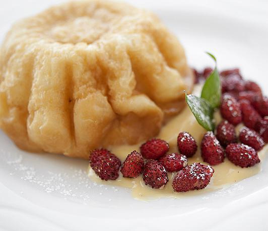 Babà napoletano, servito con crema pasticciera e fragoline di bosco