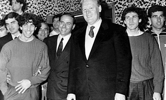 Silvio Berlusconi, da poco presidente del Milan, in visita al centro tecnico di Milanello nel marzo 1986, posa tra l'allenatore Nils Liedholm e Paolo Rossi. Sulla destra Franco Baresi e in tuta Mauro Tassotti