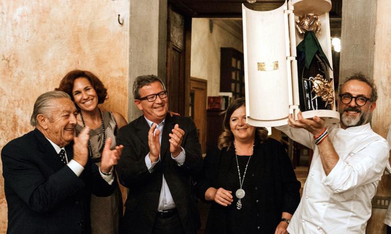 oto ricordo di una serata eccezionale il 1° luglio a Palazzo Lana in Franciacorta, suggellata dalla consegna a Massimo Bottura della straordinaria bottiglia-scultura di Arnaldo Pomodoro che ha inteso vestire così le bollicine di Berlucchi. Da sinistra verso destra il patriarca Franco Ziliani, Lara Gilmore, Arturo Ziliani, Cristina Ziliani e, infine, lo chef-patron dell'Osteria Francescana di Modena
