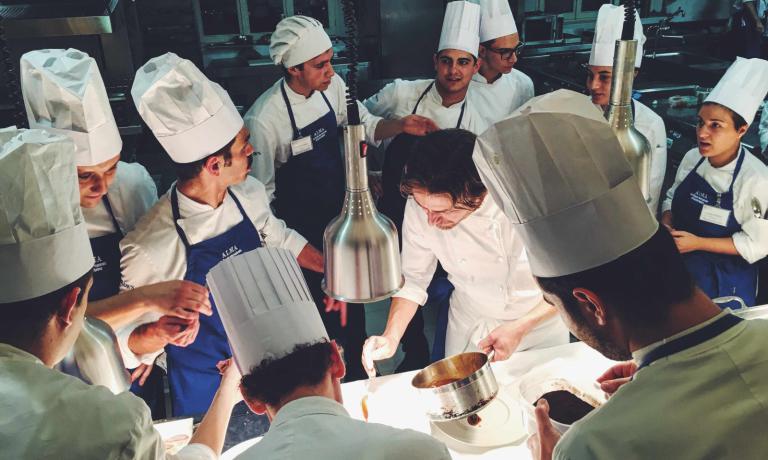 La brigata della Scuola Alma Mater osserva lo chef Baldessari mostrare l'impiattamento di una delle portate