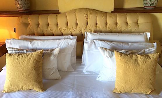 Gli otto cuscini disposti sul letto matrimoniale della stanza 25 di Casa Pavesi a Grinzane Cavour