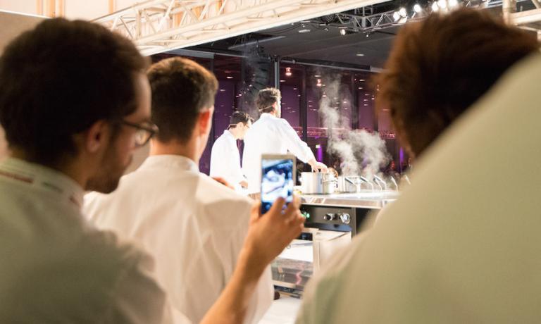 Carlo Cracco fotografato da dietro il palco dell'Auditorium di Identità Milano 2016. Il prossimo mese di marzo, Cracco terrà una lezione ogni giorno congressuale: sabato la sua visione naturale, domenica Identità di Pasta e lunedì Il Viaggio