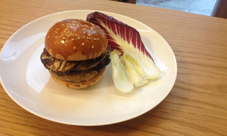 L'Hamburger di manzo di Redzepi per il Refettorio: cosparso di pangrattato, farina e uova e servito con melanzane, salsa di pomodoro e verdure miste. Il pane è pan brioche fresco