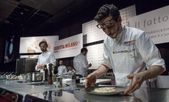Luca Sacchi, in primo piano, completa il piatto ideato da Carlo Cracco