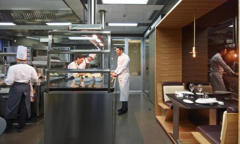 Andrea Berton nel suo regno, con il suo fedele sous-chef Claudio Catino. Sulla destra, lo speciale tavolo per due in cucina