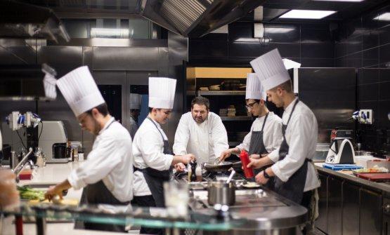 Lo chef Davide Pezzutoin cucina tra la sua brigata
