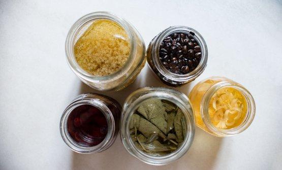 Matteo Baronetto ci spiega la sua ricerca sugli aceti aromatizzati: qui nella foto, quelli (da sinistra in alto, in senso orario) ai fiori di sambuco, al caffè, ai fiori di limone, alla salvia e all'uva fragola