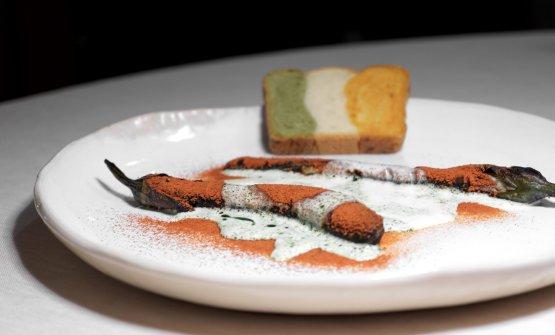 Parmigiana di melanzane: melanzana perlina fritta e glassata, polveridi pomodoro e mozzarella, olio al basilico. Si accompagna con un pan bauletto tricolore
