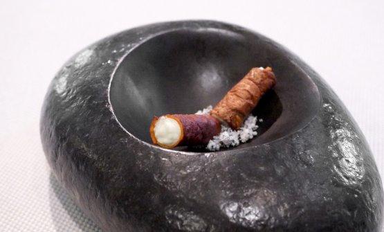 Sigaro di patate, caprino alle erbe e cenere di cipolle. Il sigaro è ottenuto con le bucce di patata