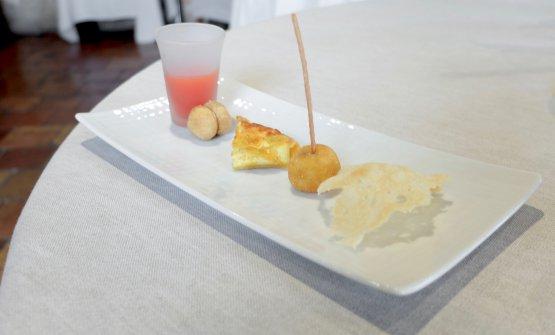 Appetizer in sequenza. Da sinistra Estratto di anguria e melone; Bacio di dama al paté di fegatini; Quiche con fiori di zucchina; Arancino alla salsiccia; Cialda al parmigiano