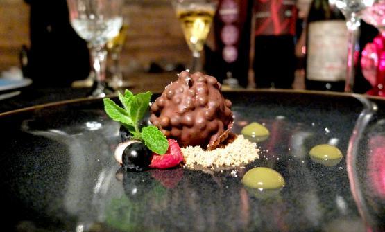 Sfera di cioccolato al latte, membrana di fondente, cuore di passion fruit, perle di cereali croccanti