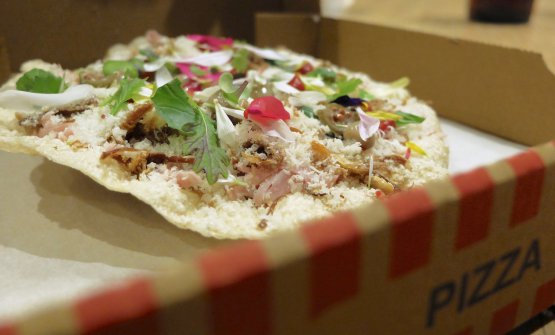 LaPizza Annadi Tokuyoshi, ossia una versione leggera della capricciosa, da condividere: la base è di riso soffiato, poi salsa di pomodoro, cialde di Parmigiano, prosciutto cotto, mortadella, capperi, acciughe e carciofi fritti. Si accompagna con brodo di capperi