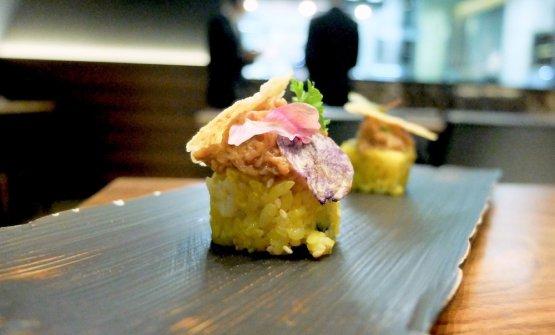Maki òs büüs: riso allo zafferano con tempura di verdure e polpa di granchio, ossobuco, chips di parmigiano reggiano, chips di patata viola e olio di scampi. Delizioso