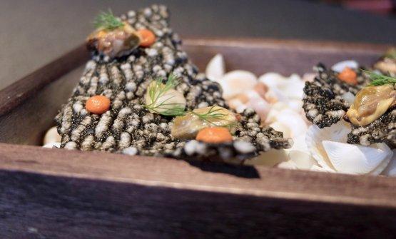Cialda di riso soffiato al nero di seppia, gel di limone, bisque di crostacei, frutti di mare