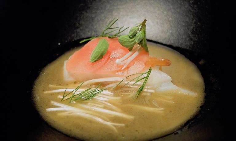 Forse il piatto, di altissima cucina,che riassume meglio di ogni altro l'evoluzione dello stile di Trentini, tra creatività piena e ancoraggio forte al gusto, anche classico: Merluzzo, brodo di funghi, rapanello sottaceto, enoki. Il merluzzo è fresco, poi salato e dissalato maison ecotto nella salamandra. Il brodo di funghi è ottenuto per estrazione a freddo di 15 giorni, non infusione, di shiitake, champignons, finferli, funghi ostrica e altre tipologie, fresche e secche, con olio evo, maggiorana, sale. Fermenta e poi viene filtrato e ridotto con del burro, alla francese