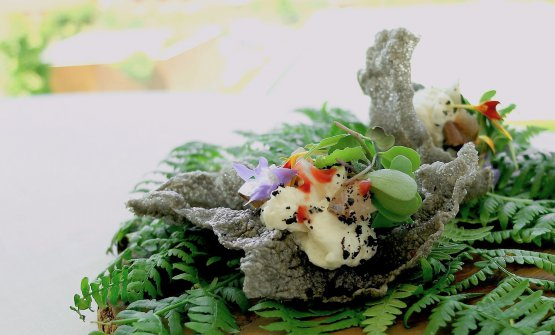 Crispy rice and ink squid wafer, herbs and flowers, cream of seafood and anchovy