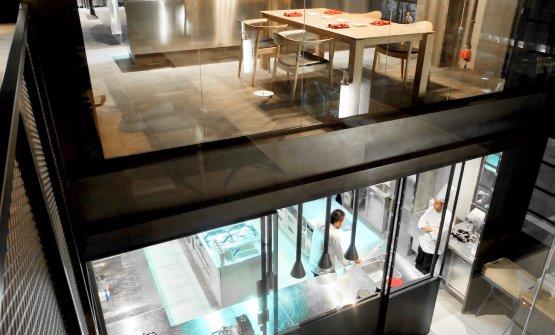 Il gioco di doppi livelli: sopra i tavoli del gastronomico, sotto la cucina del bistrot (il gastronomico ne ha una propria)