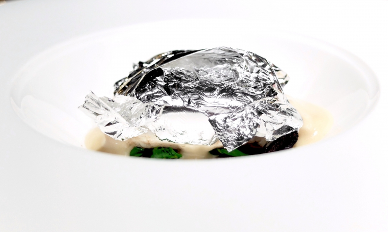 Branzino al cartoccio, olive candite e limone al sale: piatto del 2018, di Davide Oldani, che esemplifica la ricerca dello chef tra cucina, arte, design