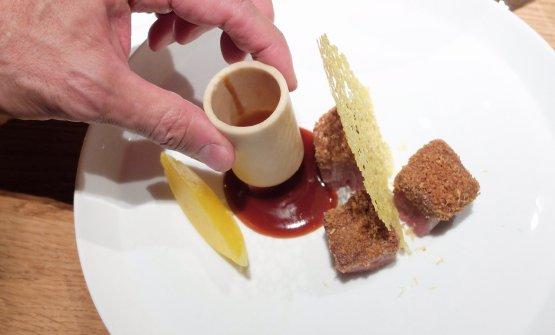 Milanese 2019: Oldani propone una sua versione della cotoletta alla milanese, con tuille di zafferano, fondo di ossobuco (la mano è dello chef, il fondo è racchiuso in un osso vero, di stinco), cubi di filetto arrosto nel pan grattato. Il finto limone è ottenutocon mela pressata e bucce di limone, appunto