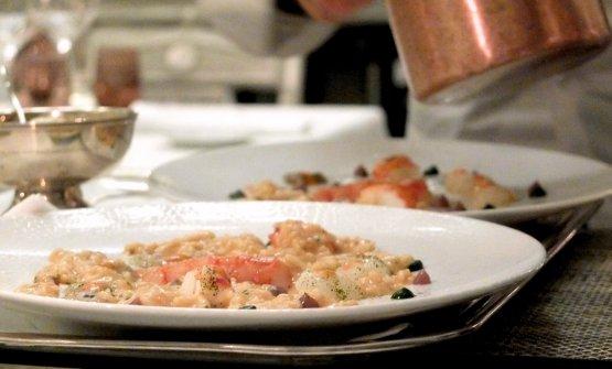 ...e conclude la preparazione diun gran Risotto allo champagne con crudo di crostacei (il loro brodetto, i ritagli di pesce crudo, le cicale marinate, il king crab, le creme d'uva edi rucola e prezzemolo, il burro francese alle erbe e agrumi, il tutto innaffiato con lo champagne). Il riso è Acquerello. Magnifica opulenza