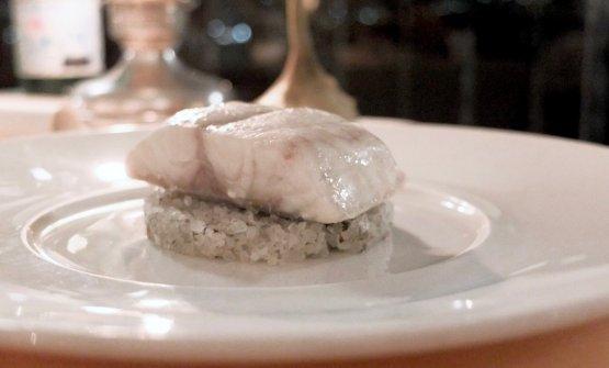 Trancio di branzino selvatico in crosta di sale, fieno, camomilla e carciofo in casseruola. È servito su una base di sale