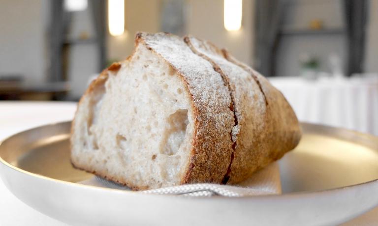 Il pane maison, da lievito madre liquido e farine 1,2 e integrale. Poi anche focaccia all'olio e grissini al mais