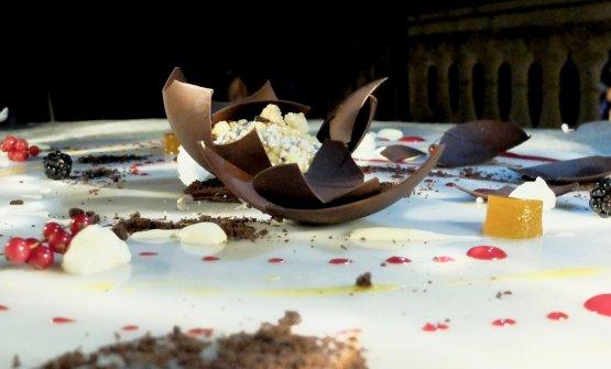 Stile Alinea: Sfera di cioccolato, salsa al passion fruit e ai frutti rossi, zuppetta di cioccolato bianco, caramello, mango, spuma allo yogurt greco, frutta fresca, terra di cioccolato, cremoso di cioccolato bianco,crumble di mandorla