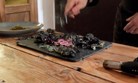 Al tavolo viene scottato un filetto di pecora gigante bergamasca racchiuso in foglie di frassino fermentate